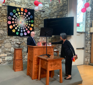 two people at church pulpit with computer set up to record