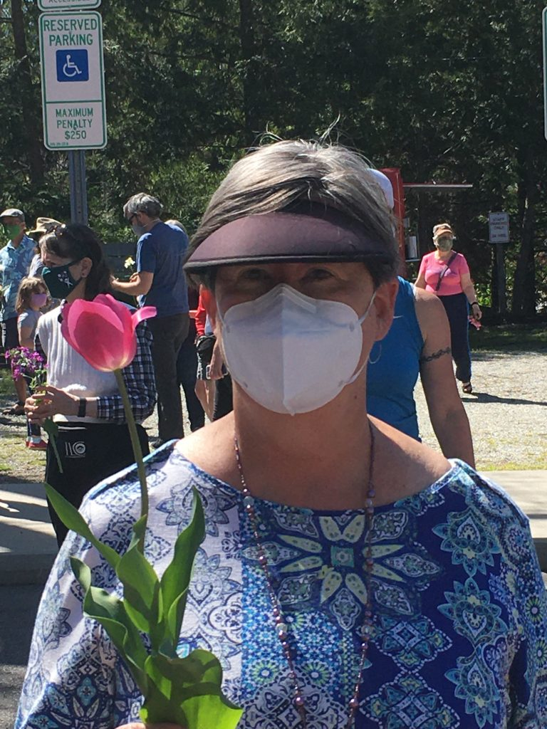 Masked woman holding flower