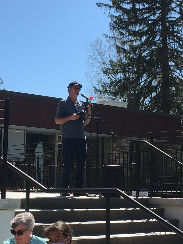 Minister casually dressed speaking at microphone outside church